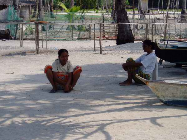 Women of the Molbog Tribe taking a rest under the shadows of coconut trees
